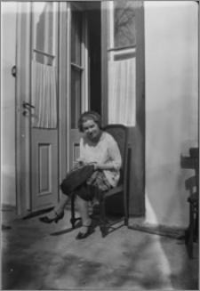 [Kobieta siedząca na krześle przed drzwiami]